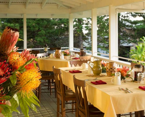 Breakfast tables and flowers on the lanai at Kalaekilohana Inn & Retreat
